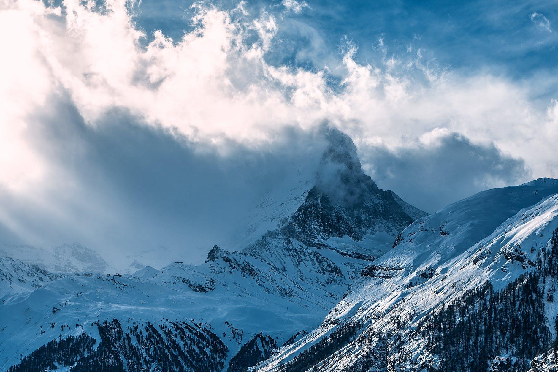snowy mountain peaks under cloudy sky in sunlight